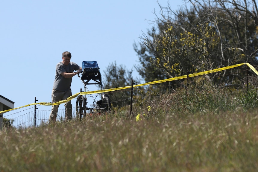 An man uses radar to search the backyard of the home of Ruben Flores with police tape near him