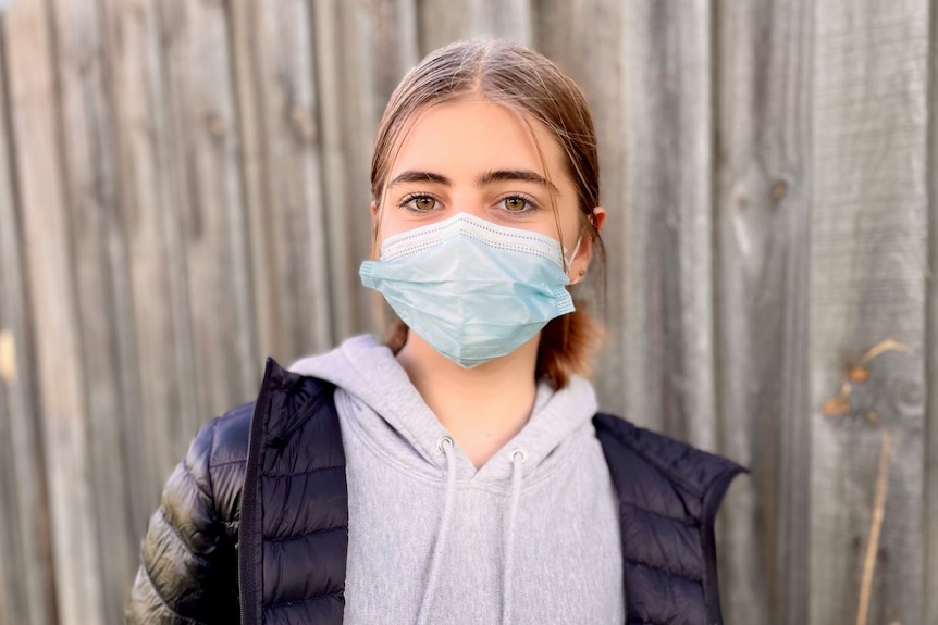 Isla Ayoub, a 12-year-old girl wearing a face mask and a puffer jacket.