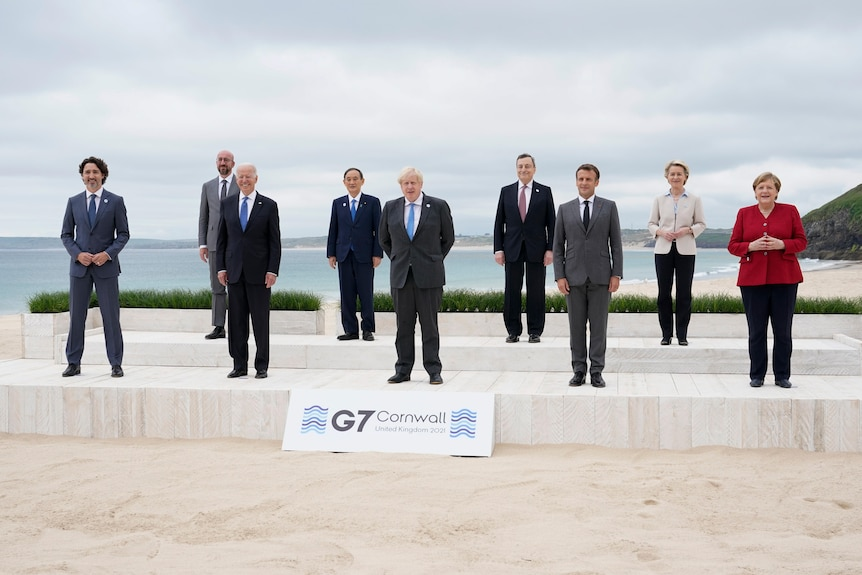 Leaders of the G7 pose for a group photo on overlooking the beach at Carbis Bay