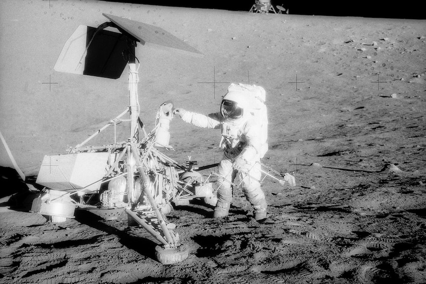 An astronaut standing next to a piece of equipment on the lunar surface