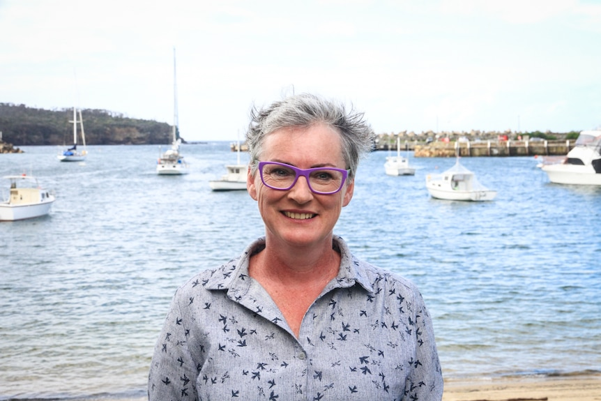 A middle-aged woman withy grey hair and purple glasses smiles with boats in a bay behind her