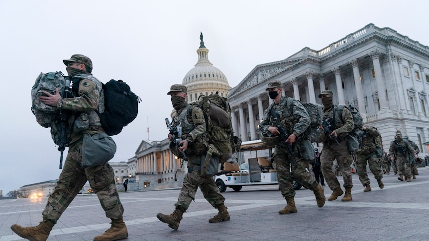 National Guard soldiers walk out of the U.S. Capitol,