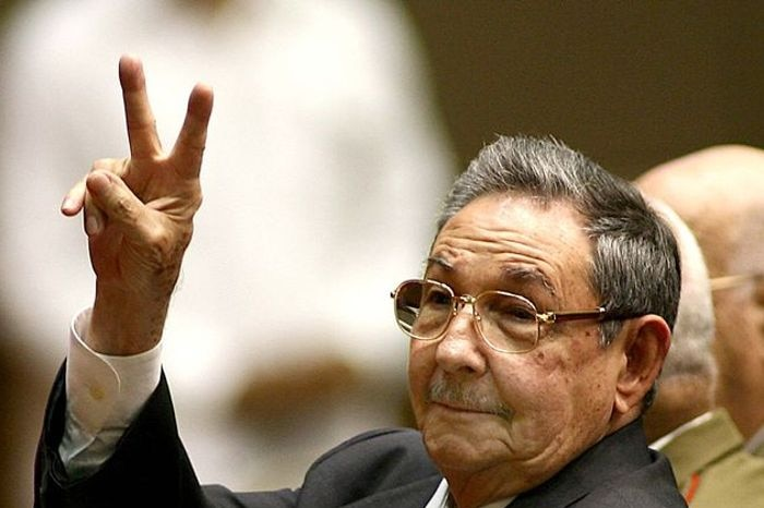 Raul Castro holding up his right hand in a v