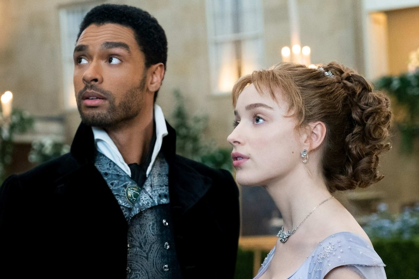 Still from the Netflix regency romance series Bridgerton with Rege-Jean Page and Phoebe Dynevor at a fancy event