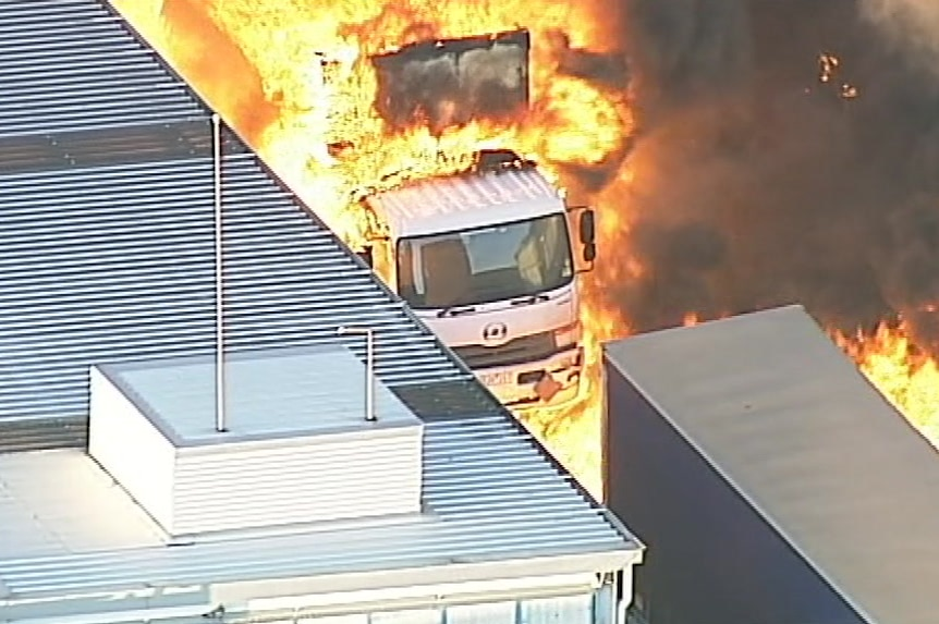 Orange flames engulf a truck as the factory fire rages.