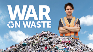 A man in a fluoro orange vest with his arms cross standing behind a pile of rubbish