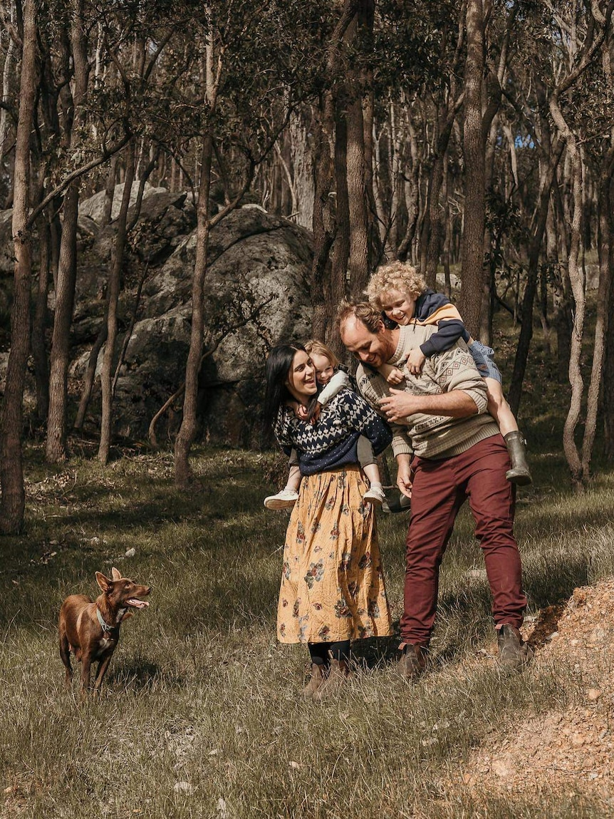 A man and woman each carrying a small child on their shoulders laugh as they walk through the bush with their dog.