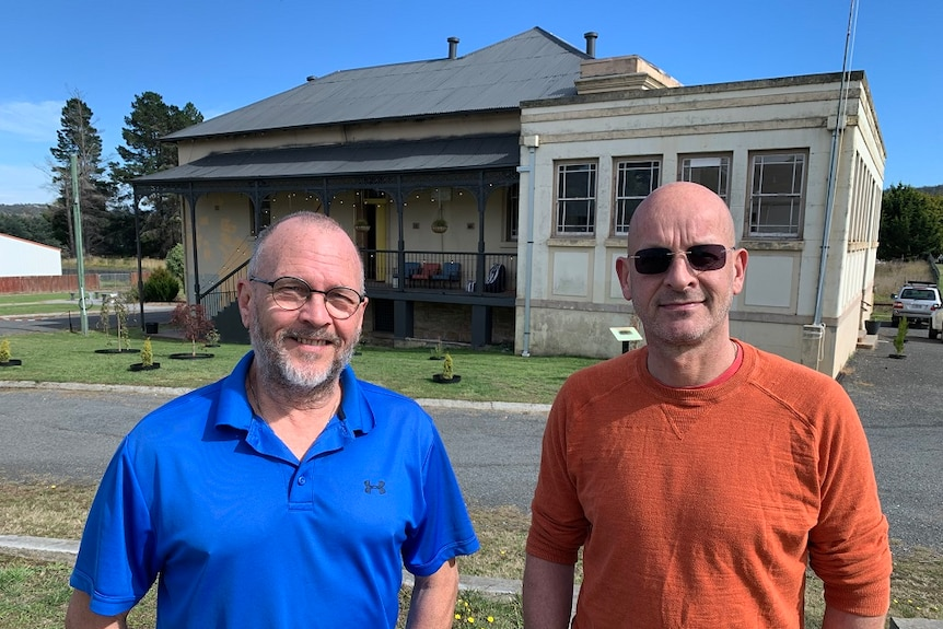Two men standing in front of an old building