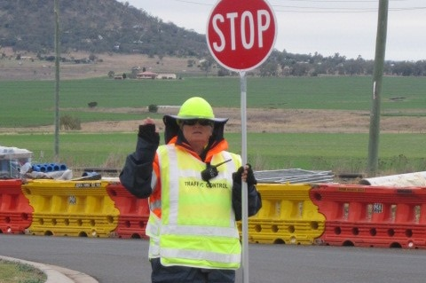 A woman wearing high-vis clothing holds a stop sign at a roadwork site.