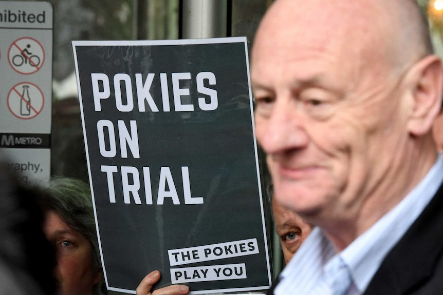 Australian Baptist minister Tim Costello stands next to a Pokies on Trial sign.