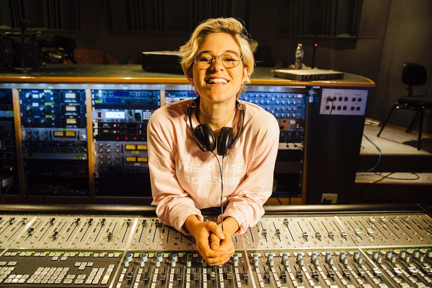 Elly Scrine sits in front of a panel in a recording studio.