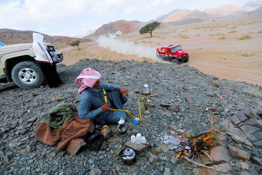 A man watches a race car drive past him in the desert