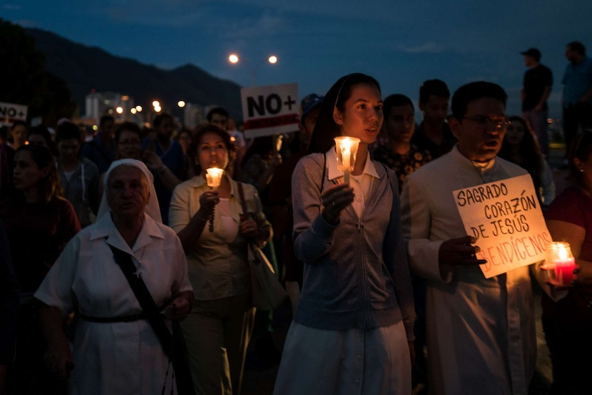 People march holding candles and signs.