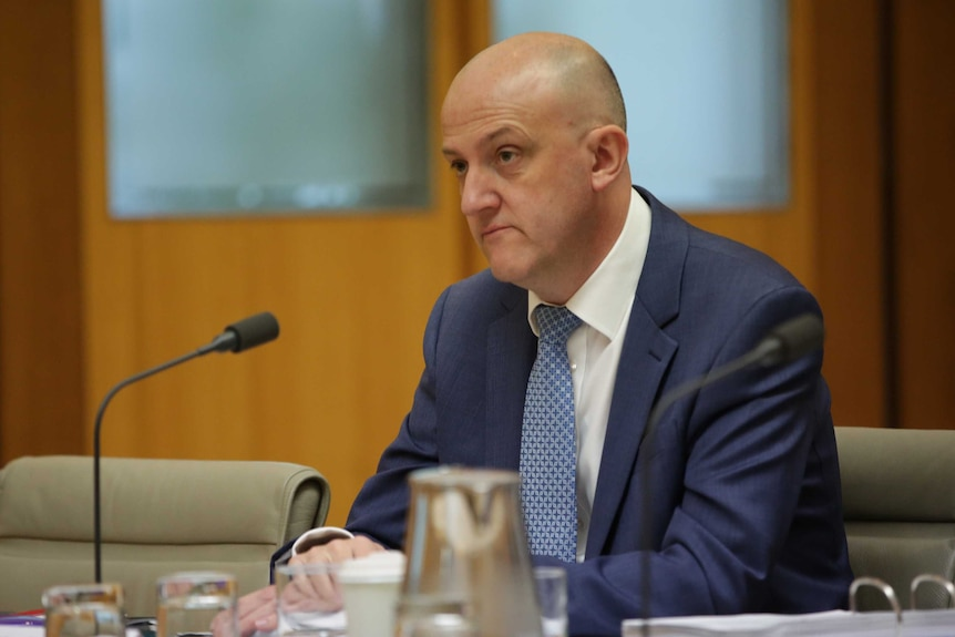 Mike Burgess sits at a table inside a committee room giving evidence to Parliament