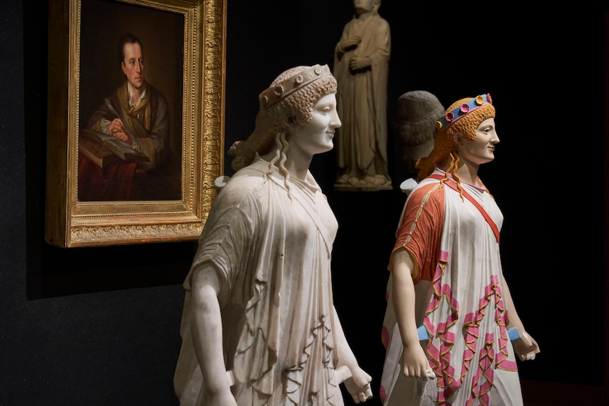 Two identical statues that appear to be on Ancient Greek origin, one is in colour