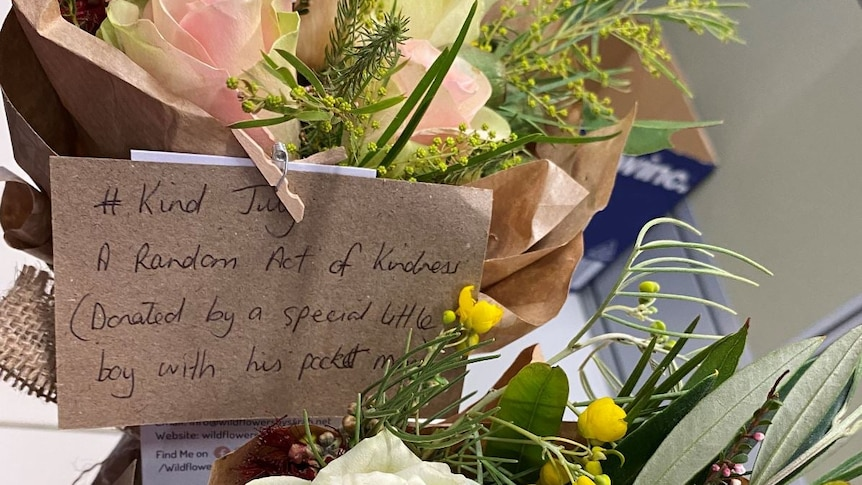 A bouquet of flowers with a note attached, that reads '#Kind July, a random act of kindness