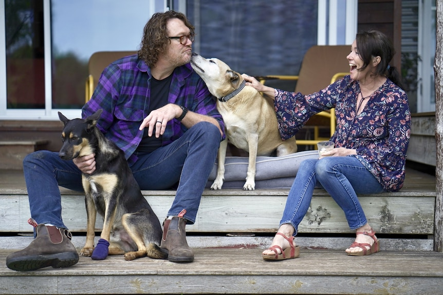 A man wearing glasses leans in for a 'kiss' from his dog as a woman laughs. The pair sit on a deck