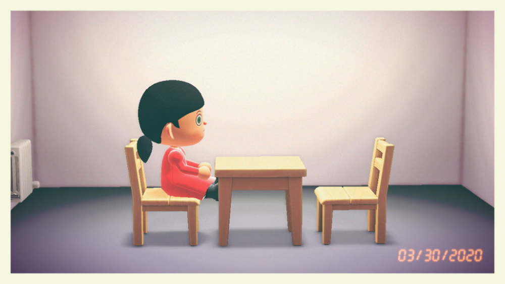 A photo of 3D game character with dark ponytail and red dress sits at wooden table on chair opposite empty chair in empty room.