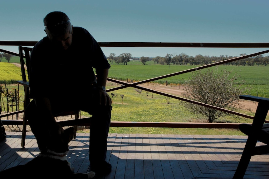A man in silhouette sits on a veranda with farmland behind him