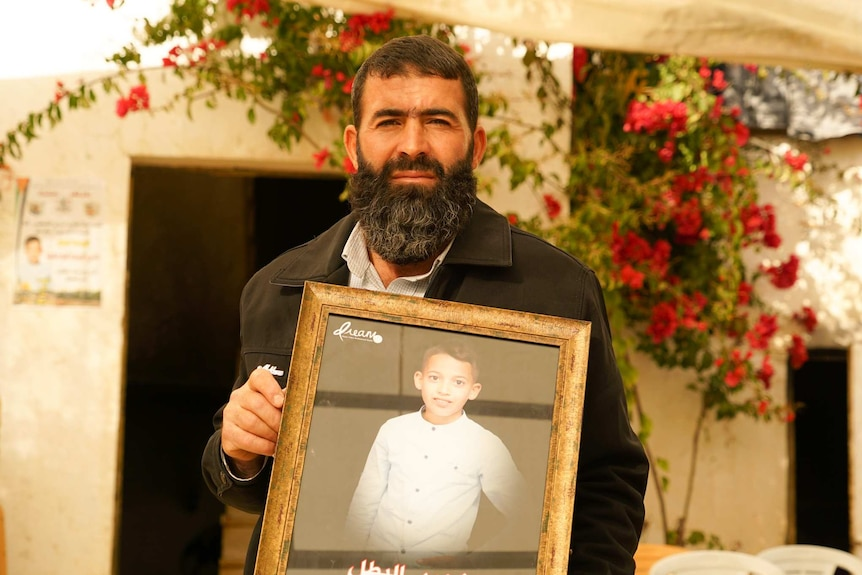 A man with dark hair and a beard holds a photo of a young boy in a white shirt outside under a shade.
