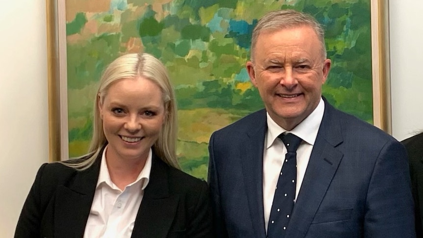 A young blonde woman, Anthony Albanese, and a young brunette woman stand side by side in front of a green painting.