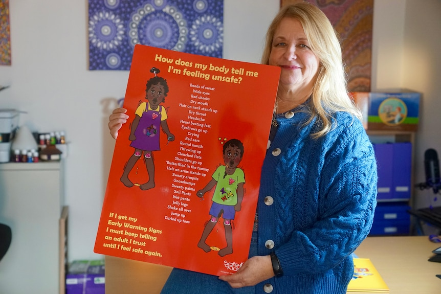 A smiling woman holds up a large poster