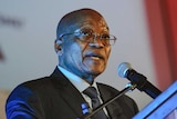 South African President Jacob Zuma speaks at a lectern.