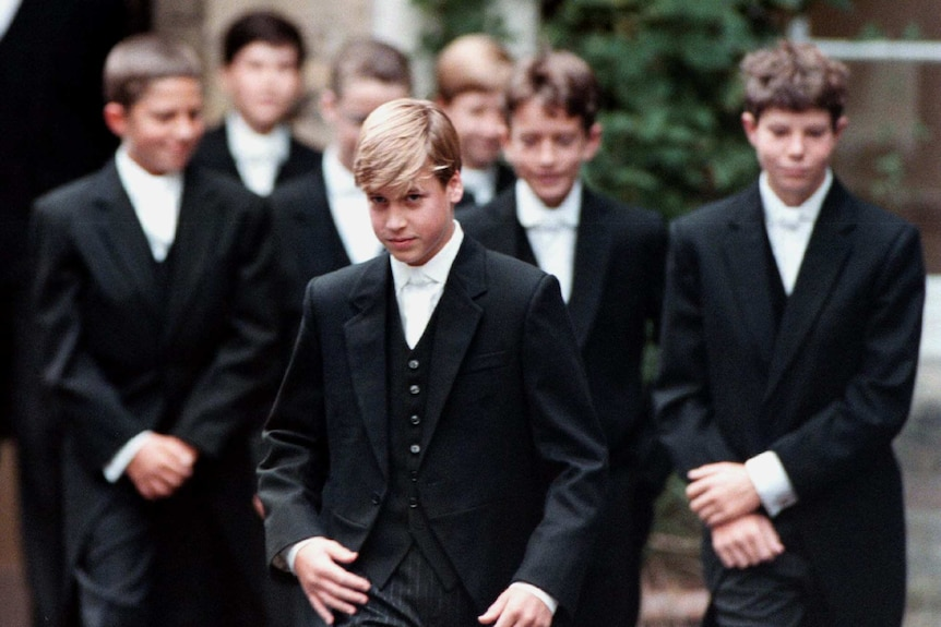 A young Prince William is dressed in Eton College's formal three-breasted suit uniform and walks with classmates.