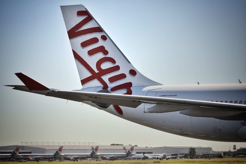 Close-up of tail of a Virgin Australia aircraft with other Jetstar aircraft in distance at Brisbane Airport.