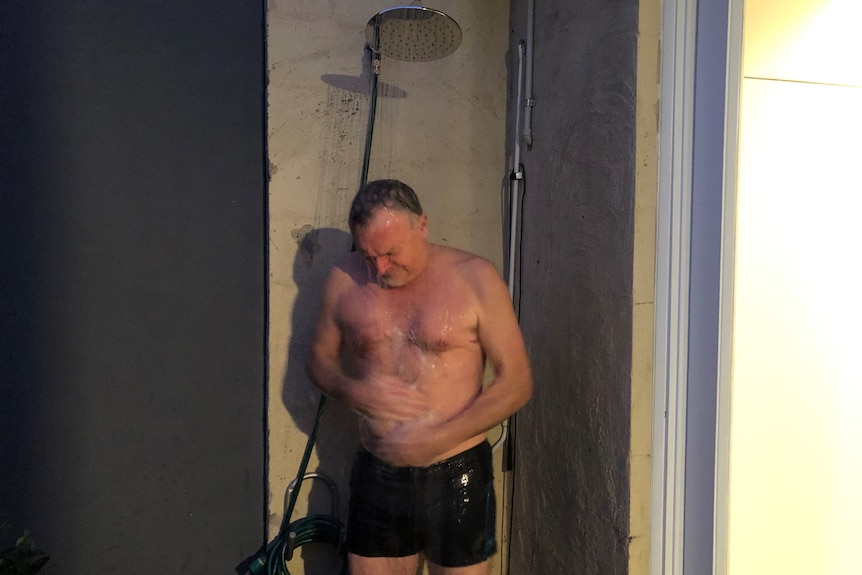 A middle-aged man in board shorts standing under a running shower connected to a garden hose