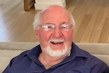 A photo of an older man smiling while wearing glasses