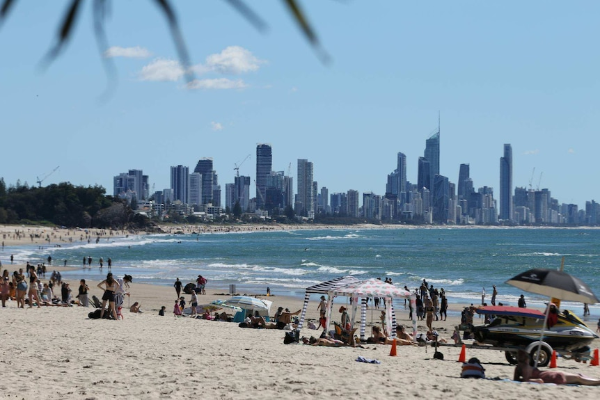 Beach is busy with people and city skyline in background.