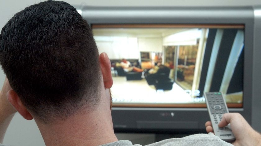 A man watches TV while sitting in a lounge chair
