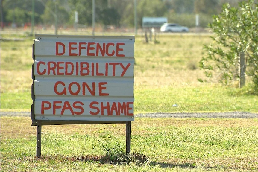 """A sign reads """"Defence Credibility Gone - PFAS Shame"""""""