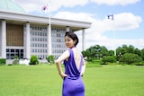 A young Korean woman in a low backed purple dress with tattoos across her back