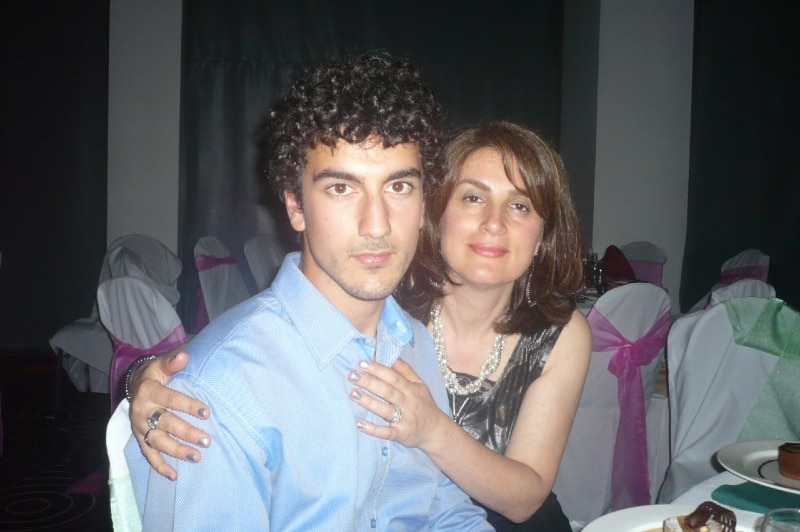 A young man sitting at a table at a family function with his mother with her arms around him.