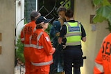 Police and SES officers speak to a neighbour in Malvern.