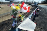 Flowers and a Canadian flag are tied by the road side.