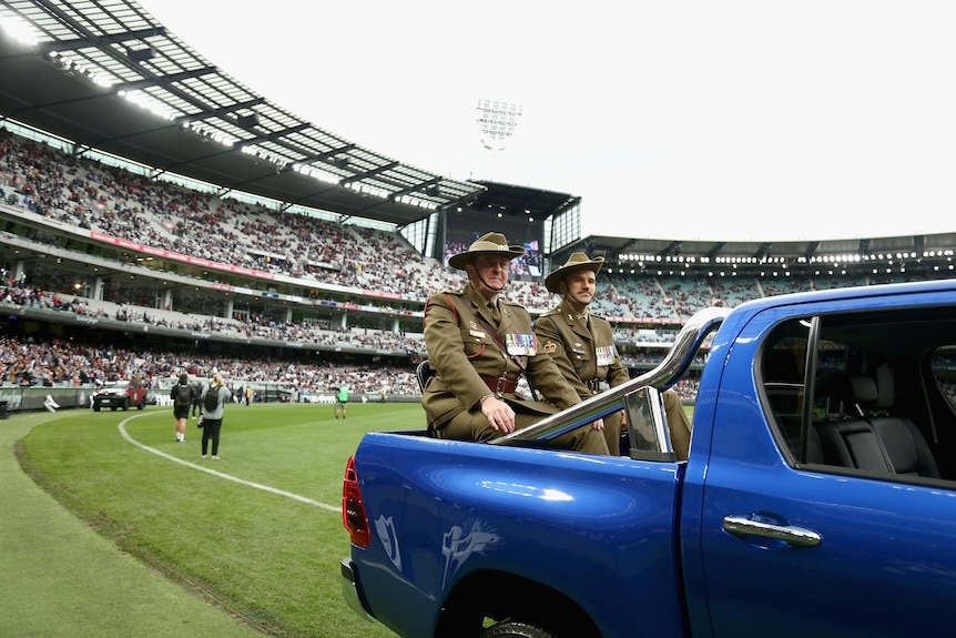 Two men in military clothes sit in the back of a ute at the Anzac Day AFL game between Essendon and Collingwood.