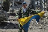 Pro-Russian rebel displays seized Ukrainian flag in Luhansk