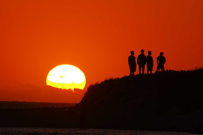 Four figures in silhouette standing on headland watching sunset amid red sky