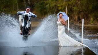 Gavin drives a motorbike through a puddle past his wife in her wedding dress.