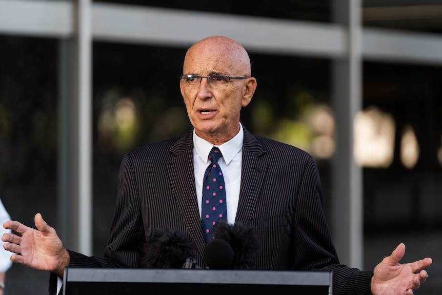 Man in suit speaks behind podium