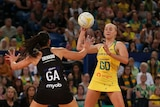 Netballer in the action of throwing the ball with defender with her arms up during a match