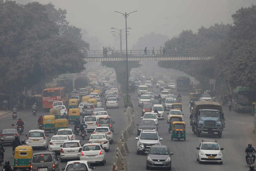 Several lanes of traffic drive through smog that limits visibility.