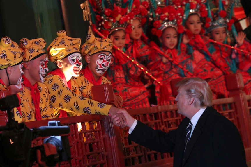 Donald Trump shakes hands with one of many opera performers during his visit to China.