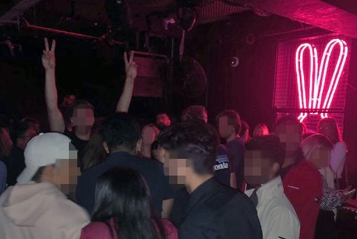 A crowd of people standing on a dancefloor in a nightclub