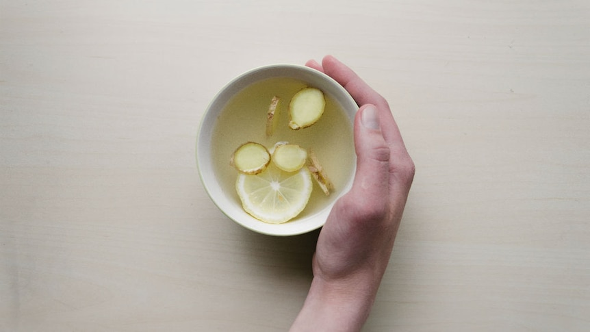 A hand cradles a mug with slices of lemon and ginger in hot water.