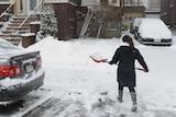 A woman shovels snow on Bayswater Street in East Boston, Massachusetts.