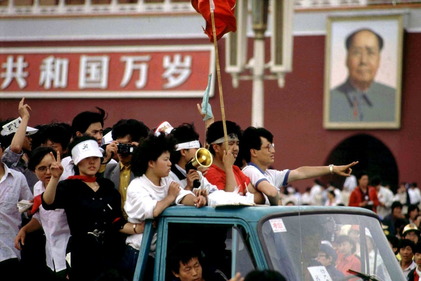 Student protesters arriving at Tiananmen Square ride past a portrait of Mao, they are riding in a ute or truck